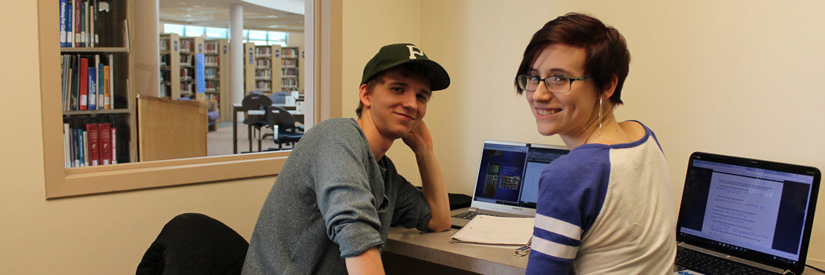 two students smiling in a study room with library stacks behind them through a window